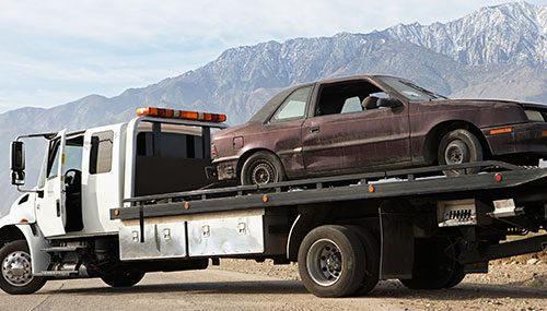 Image of Phoenix Towing Service truck towing away an old car.