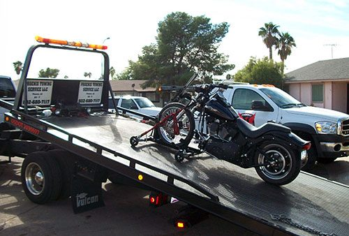 Image of Phoenix Towing Service truck towing away a motorcycle.