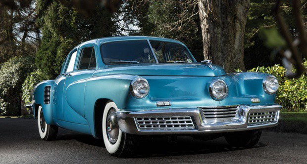Image of a blue Tucker 48 parked in a forest.