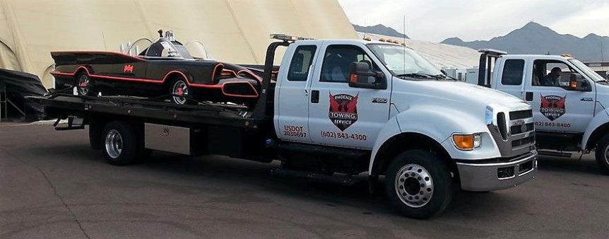 Image of Phoenix Towing Service tow truck towing a vintage car to a car show.