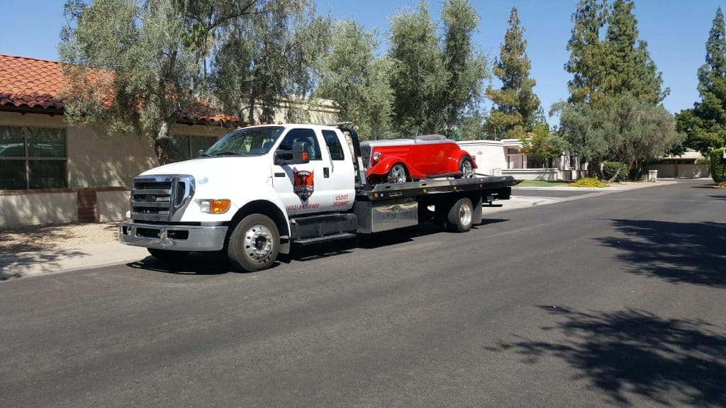 A photo of Red Roadster being towed