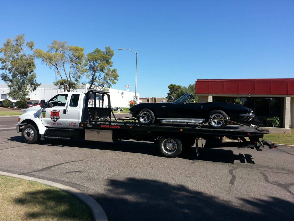 A photo of Black Corvette being towed