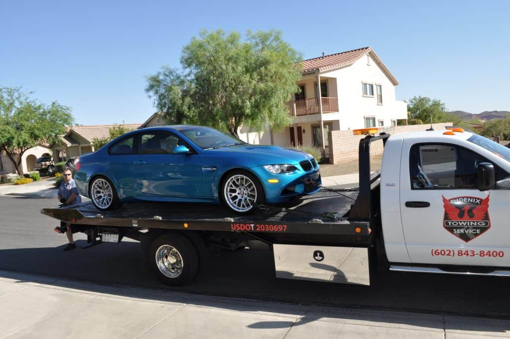 A photo of a blue BMW being towed in Phoenix