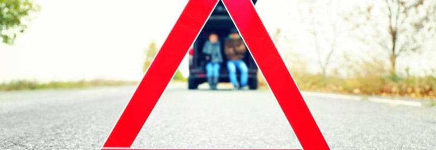 Image of couple leaning against a broken down car waiting for emergency towing services.