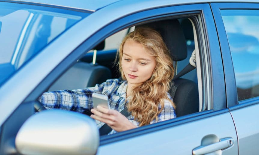 Woman using her smartphone while driving a car