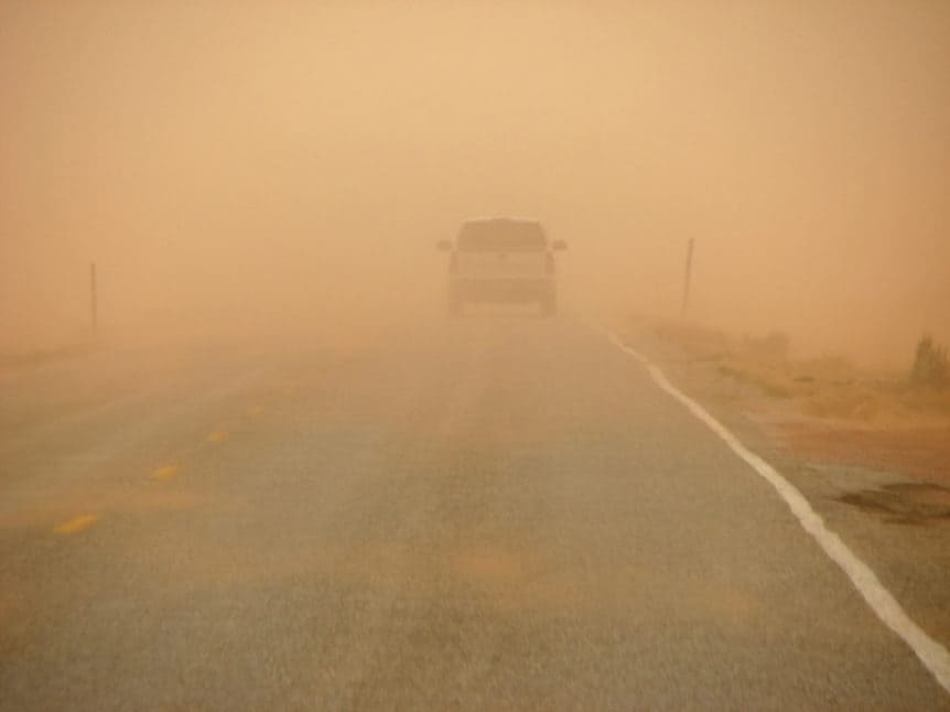 driving along a highway into an orange sandstorm in Arizona, visibility is reduced drastically
