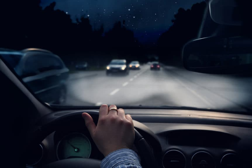 image of a man driving a car in the night