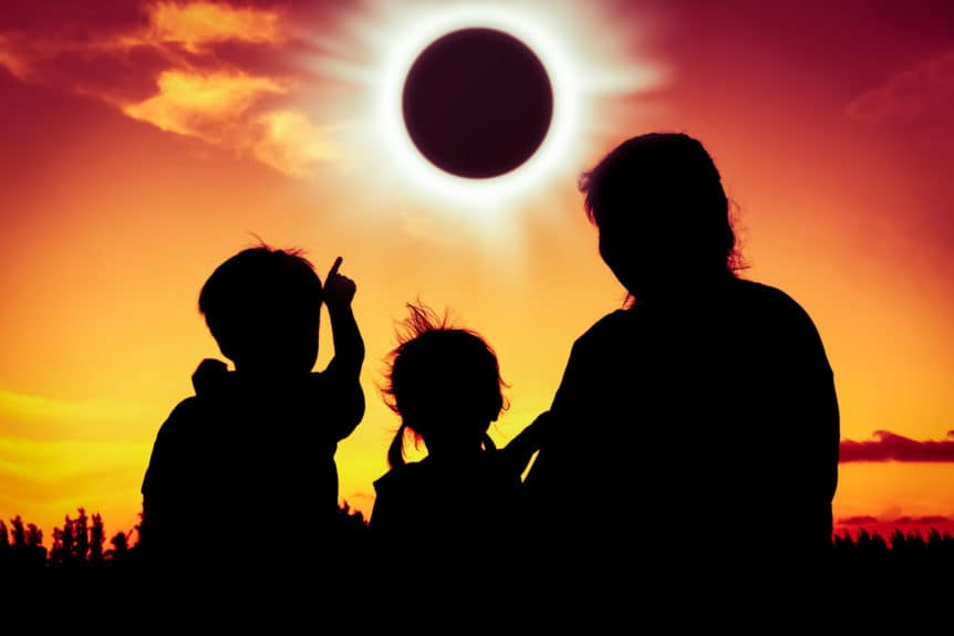 Image of a natural phenomenon. Silhouette back view of family sitting and relaxing together. Boy point to solar eclipse on gold sky background. Happy family spending time together. Outdoor.