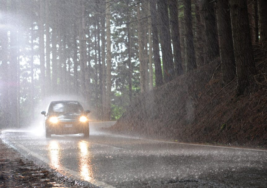 Car riding under heavy rainfall with its headlights on