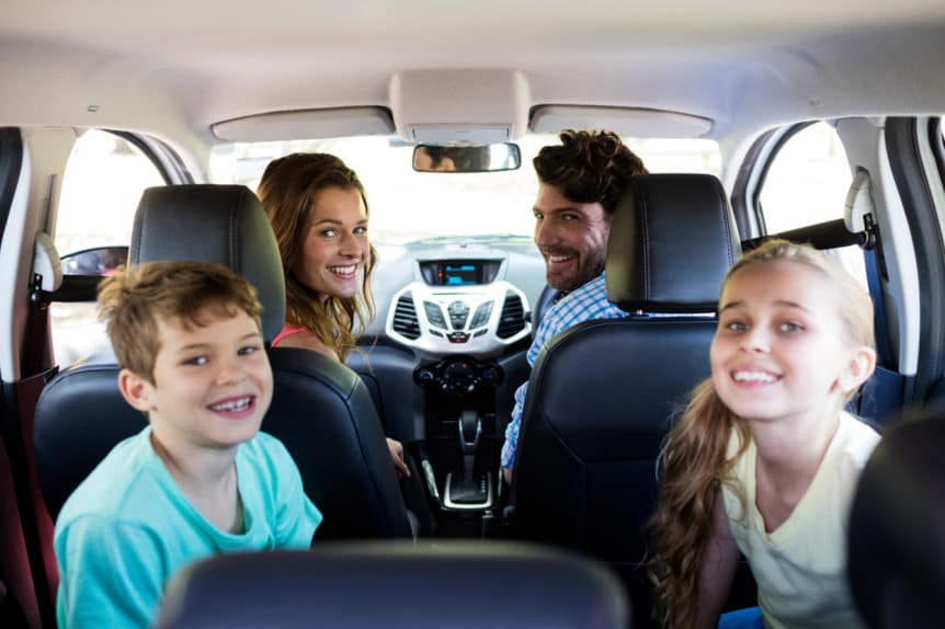 Portrait of happy family sitting in car