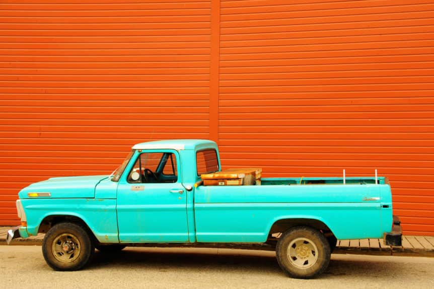 A shot of a old rusty blue truck up against a red wall in Skagway, Alaska.