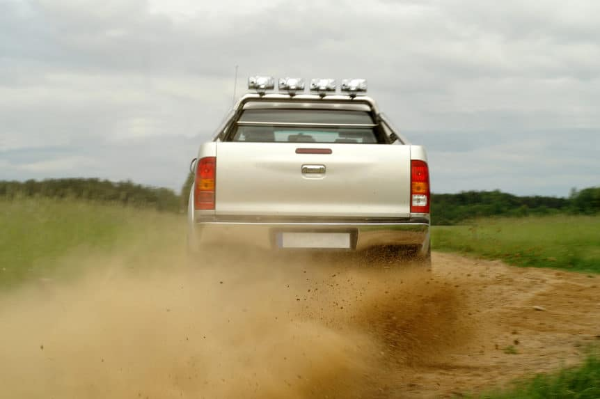 Back view of a pickup truck drifting on gravel road