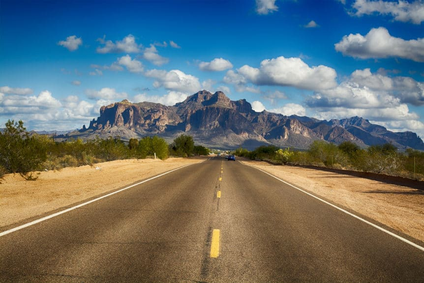 A long remote road leading to the base of famous Superstition Mountain in Arizona shows the beauty of this desert landscape. Concept of the Most Dangerous Roads in Arizona.