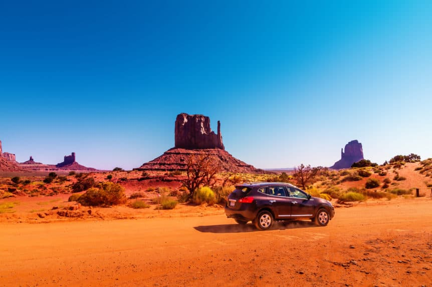 Car on the Monument Valley drive. The Valley Drive is a scenic dirt road through Navajo Tribal Park on the border of Arizona and Utah with beautiful views to spires, buttes and red rock creations.