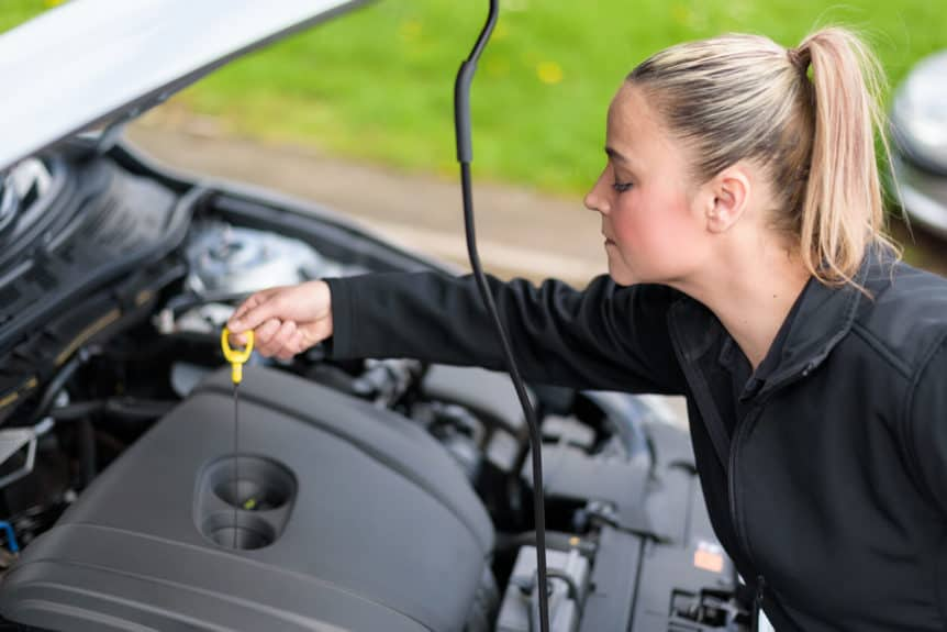 Preparation for Drives Woman checking a car's oil level