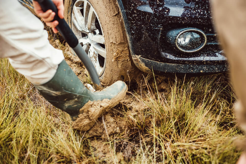 Man-digs-excavates-mud-with-shovel-to-get-the-car-out What to Do if Your Car Gets Stuck in the Mud?