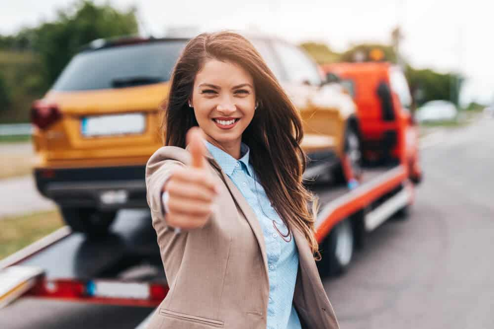 Elegant middle age business woman is happy and satisfied with fast and reliable towing service for help on the road.
