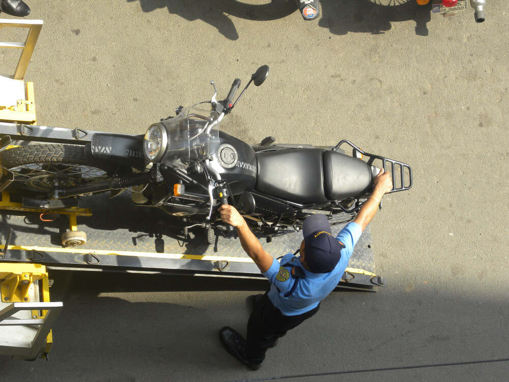Bangalore, Karnataka, India - June 2 2018 a Security Guard Towing a Black Color Motorcycle on the Tow Truck